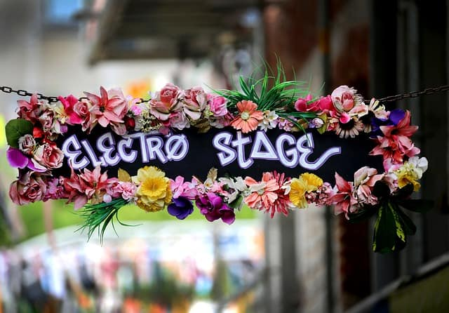 A flowered hanging sign with the text Electro Stage