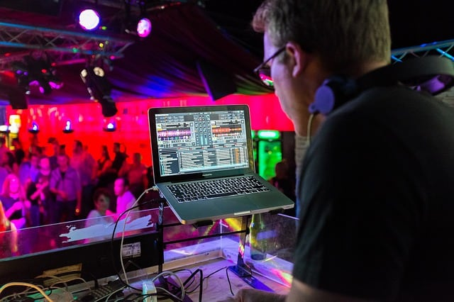 A male disc jockey (DJ) that is playing two tracks at the same time on his laptop