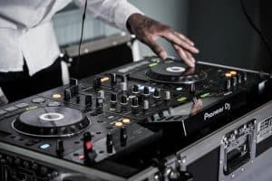 A DJ is performing on his Pioneer DJ gear