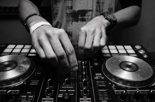 A DJ is mixing tracks on a DJ controller