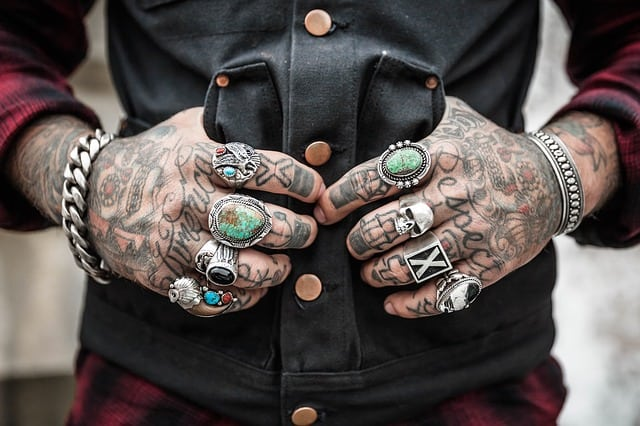 A person with tattoed hands and arms, and with rings and bracelets