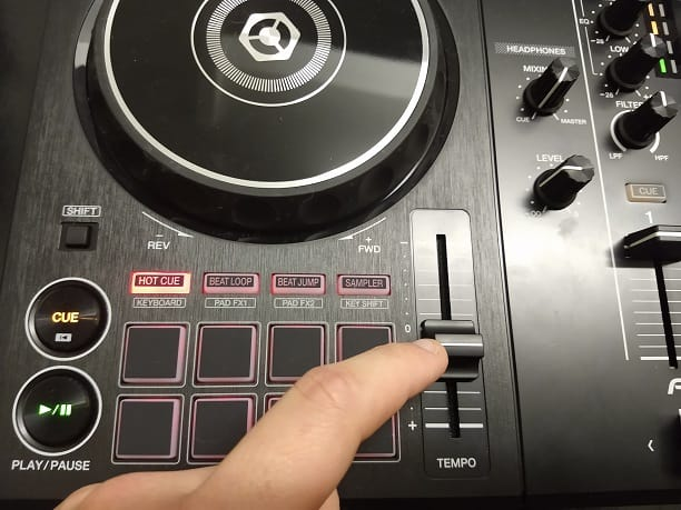 A finger pointing to a tempo slider of a Pioneer DDJ-400 DJ controller