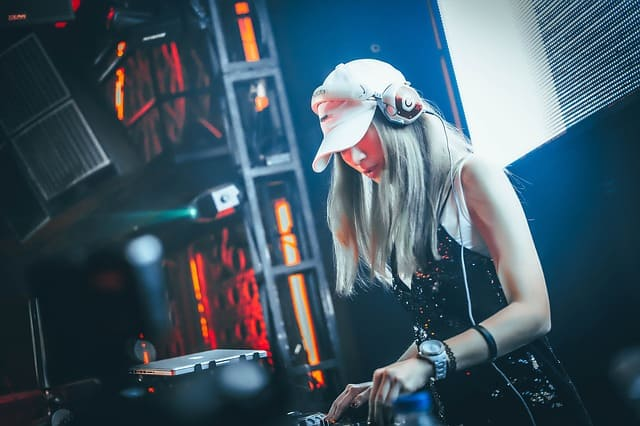 A female DJ wearing headphones that is part of her style