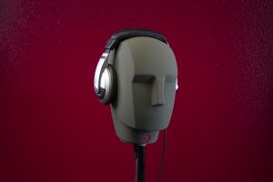 A dummy male head with headphones on it