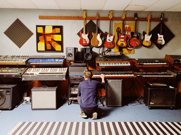 A man touching a synthesizer in a place with more music equipment