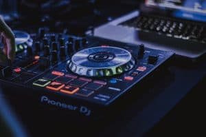 A DJ controller from Pioneer DJ next to a laptop