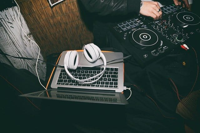 Someone with a DJ controller, laptop, and headphones
