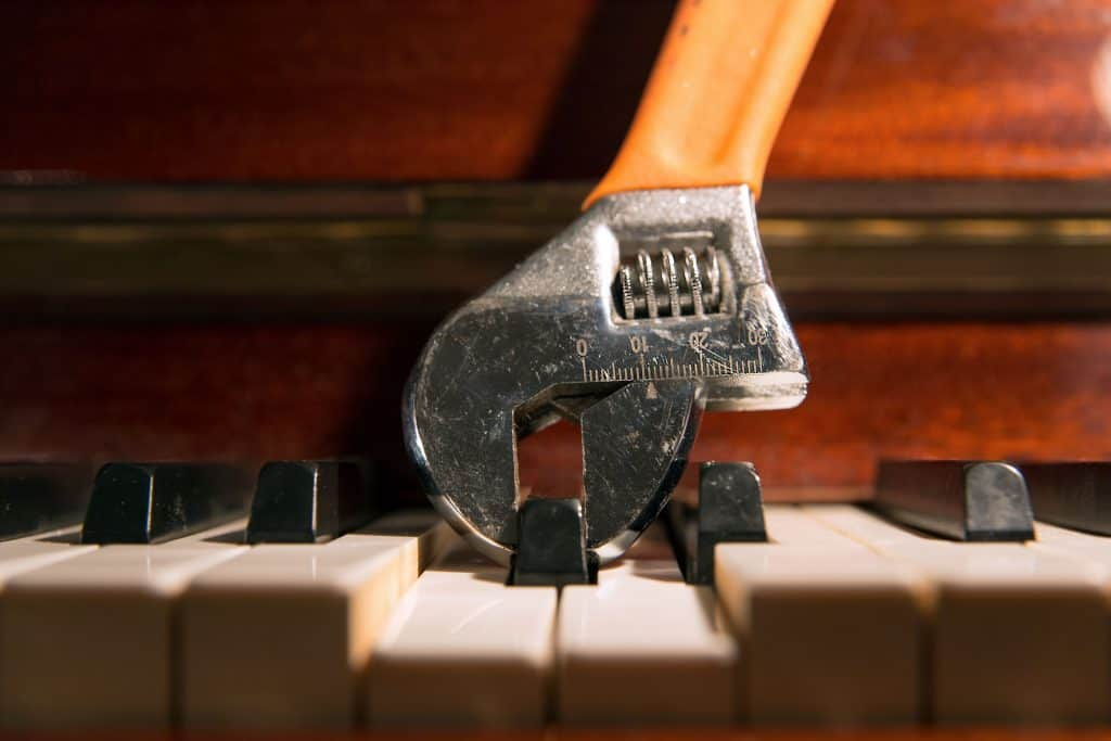 An adjustable wrench holding a piano key