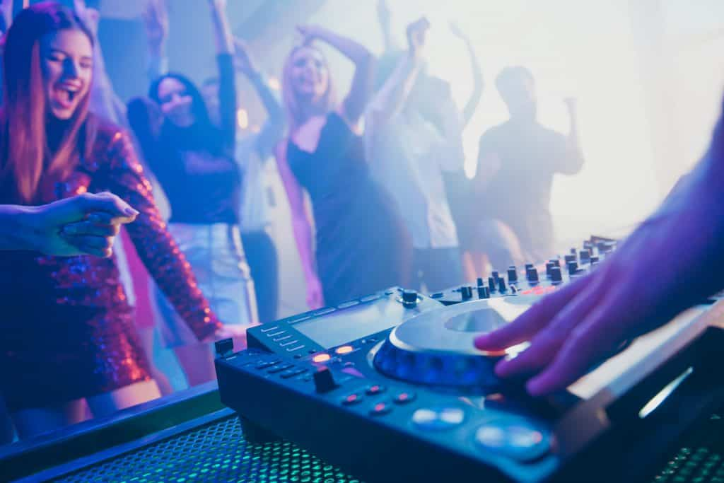 DJ playing stereo loud sound rhythm set for attractive, stylish, cheerful positive people crowd to hang out enjoying evening having fun time festive concert at a fashionable modern nightclub