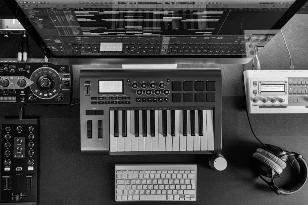 Flat top lay home music studio DJ and producer equipment on the black table (Black and white)