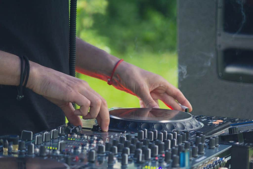 DJ playing disco house progressive electro music at the concert. DJ has his hands on equipment
